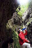 Woman hiking in the Gorge, Partnachklamm, Woman taking a break and having a drink, Garmisch-Partenkirchen, Bavaria, Germany