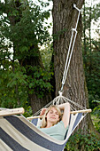 Middle aged woman lying in a hammock, relaxation, Bavaria, Germany