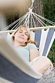 Frau mittleren Alters liegt in einer Hängematte, Entspannung, Bayern, Deutschland