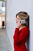 Middle aged woman talking on a mobile phone, Pinakothek der Moderne, Munich, Bavaria, Germany