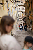Mother and child walking down a small alley in the old town of Grasse, Cote d'Azur, Provence, France