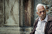 Old man outside of a church. Sicily, Italy