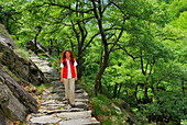 Mid adult woman walking over cobbled path, Ticino, Switzerland