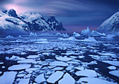 Ice floes near the Antarctic Circle with lenticularis cloud over mountain peak, Antarctic Peninsula,  Antarctica