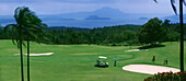 People at golf course of Tagaytay Country Club with Taal Volcano, Tagaytay, Luzon Island , Philippines, Asia
