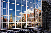 Reflection of St. John's Church and gabled houses in glass front, Luneburg, Lower Saxony, Germany