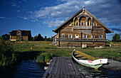 Traditional Russian wooden houses (early 191th- 20th century), pier and boat, Vasilevo. Kizhi island, Onega lake, Karelia, Russia