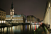 Hamburgs World War 1 Memorial, Rathaus, Alster Arkaden and the Alster River by night in Hamburg, Germany.