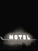 The glowing neon sign for an inexpensive motel is captured in Black and White at night.