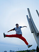 Asian (Chinese) young man straddle jumping facing down to the camera, sky has been blue-saturated