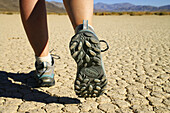 Female hikers feet and boots on cracked mud of desert playa at the Racetrack, Death Valley National Park, California, USA