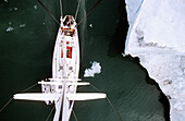 View down from top of mast to deck of sailing boat passing iceberg, Kings Bay, Svalbard, Spitzbergen, Norway