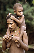 Koroway woman carrying her child on her shoulders, Western Papuasia, Former Irian-Jaya, Indonesia