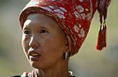 An ethnic red dao (Dao Do, Yao, Mien) woman from Northern Vietnam wearing a tall red turban, Lao Cai province. Vietnam.