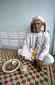 An ethnic Cham man named Ong Quan enjoys a cup of tea on his patio in Tuan Tu village. Ninh Thuan province. Vietnam.