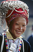An ethnic Red Dao woman from Northern Vietnam wears a red turban decorated with silver. Muong Hum. Lao Cai province. Vietnam.
