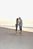 Couple in their 20s kissing on the beach of ocean city by the drawing of heart and arrow and their initials
