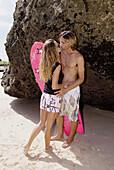 surfer kissing girl friend on the beach