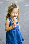 3-year old girl with an ice cream cone in Boston Public Garden. USA.