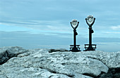 Binoculars overlooking a rocky shore, Maine, USA
