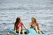girl 13, girl 18 yrs on lake in paddleboat
