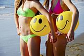 girl 13, girl 18 yrs standing on beach holding smile beach balls