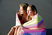 girl 13 and girl 18 wrapped in towel together on beach, sisters