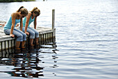 girl 13 girl 18 sitting on dock together looking at water