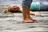 legs of girl 18 standing girl 13 laying on dock on lake