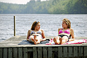 sisters 13 and 18, laying on dock talking and suntanning together