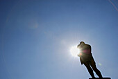 statue of man arms folded with sun peeking through