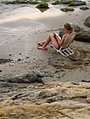 Adult, Adults, Alone, Beach, Beach chair, Beach chairs, Beaches, Bikini, Bikinis, Book, Books, Calm, Calmness, Chill out, Chilling out, Color, Colour, Contemporary, Daytime, Deck chair, Deckchair, Exterior, Female, Full-body, Full-length, Hobbies, Hobby,