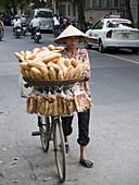 A bread vendor pedals her wares. Haiphong city, Vietnam (april 2006)