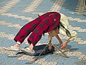 the amazing acrobat, girl on street corner in Lijiang, China