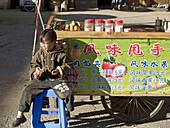 boy sits in front of fruit shake vendor, Shangri La, China