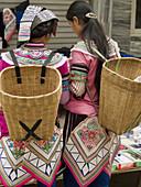 Yi women with their skirts, market, Yuanyang, China