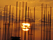 Sunrise behind the steel bar structure of a building construction work. Pune, Maharashtra, India.