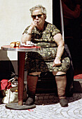 Robust woman at table outside cafe, drinking coffee, with knee highs showing