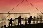Aktivität, Angestellte, Angestellter, Arbeiten, Arbeitend, Arbeitende, Arbeiter, Außen, Bau, Beruf, Berufe, Drei, Drei Personen, Eisen, Erbauen, Erwachsene, Erwachsener, Farbe, Form(formular), Gerüst, Gerüste, Gewellte rute, Hart, Hintergrundbeleuchtung,