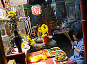 Older woman with incense sticks in San Cha Phuo Sua Temple, Phra Nathon quarter, Bangkok, Thailand