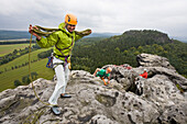A young woman collects the rope on the summit of Papststein, Elbe Sandstone Mountains, Saxon Switzerland, Saxony, Germany