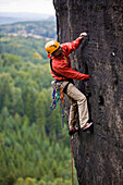 A young man climbing on rock, Grosse Hunskirche, Papststein, Elbe Sandstone Mountains, Saxon Switzerland, Saxony, Germany