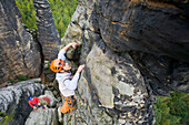A young man rock climbing at the small Hercules Column, Alter Weg in Bielatal, Elbe Sandstone Mountains, Saxon Switzerland, Saxony, Germany