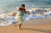 Fisherman with a net full of fish on the beach of Mazunte, Mexico