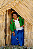 Indigenous woman of the Uros people in front of a reef hut, Lake Titicaca, Peru, South America