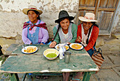 Three indigenous women having lunch in Tarabuco, Bolivia, South America