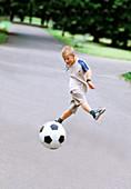 Boy playing soccer in park, summer, Krakow, Poland