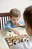 30-40 years, 5 to 10 years, 5-10 years, 6-7 years, Boy, Caretaker, Caucasian, Chess, Chessboard, Child, Color, Colour, Contemporary, Educate, Education, Father, Game, Home, Indoor, Indoors, Inside, Interior, Kid, Learn, Learning, Parent, Play, Playing, Sk