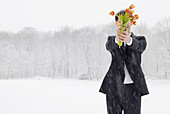 Young man holding a bunch of tulips standing in snow flurry, Munich, Bavaria, Germany