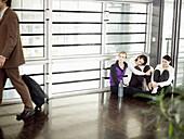 Three businesswomen watching businessman, Munich, Bavaria, Germany
